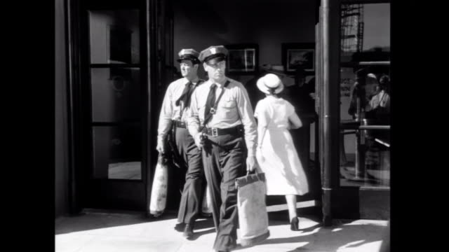 1952 Armed guards transport cash from a bank as a man observes from a nearby window