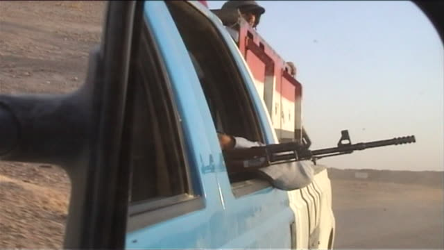 vídeos de stock, filmes e b-roll de cu zi armed iraqi officer with rifle seen in mirror of convoy vehicle, barwana, al anbar, iraq - iraq