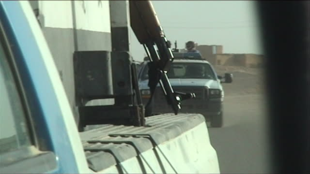 CU ZI SHAKY Armed Iraqi officers seen in rearview mirror of convoy vehicle, Barwana, Al Anbar, Iraq