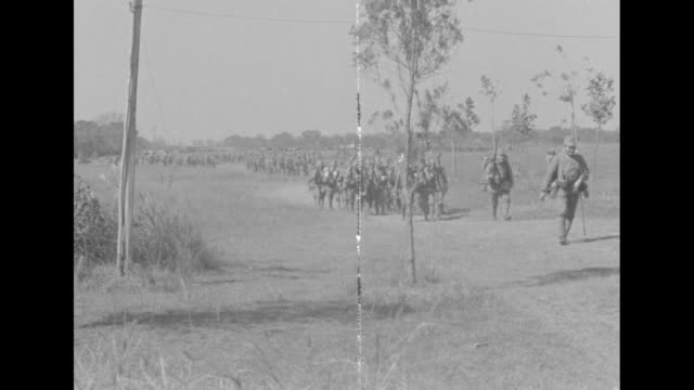 armed japanese soldiers march past camera and walk along dusty country carrying ladders and pulling loaded carts / a line of japanese field guns... - 日本の軍事力点の映像素材/bロール