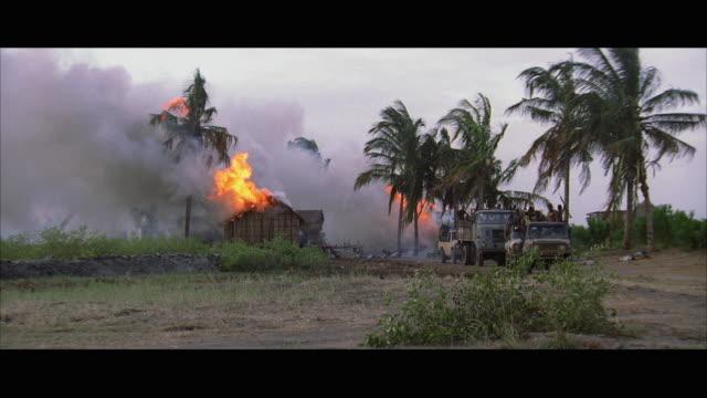 vídeos de stock e filmes b-roll de ws armed marauding rebels flee from burning village - formato letterbox