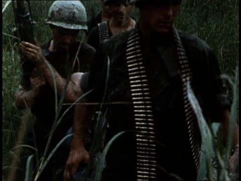 armed marines trudging through heavy vegetation and water / south vietnam - 南ベトナム点の映像素材/bロール
