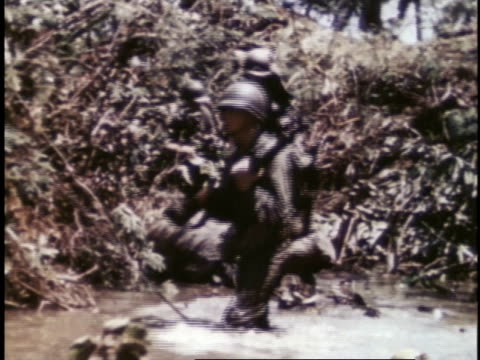 armed marines wading through water and struggling through brush / guam - guam stock videos & royalty-free footage