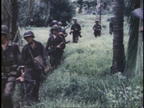 armed marines walking single-file through grass / guam - pacific war stock videos & royalty-free footage