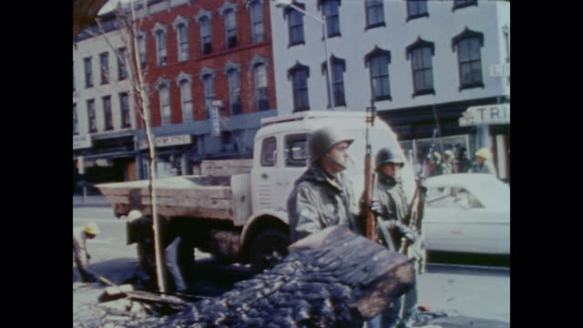 vídeos y material grabado en eventos de stock de armed national guard soldiers patrol and guard streets during post riot clean up as passersby and residents watch from afar - 1968