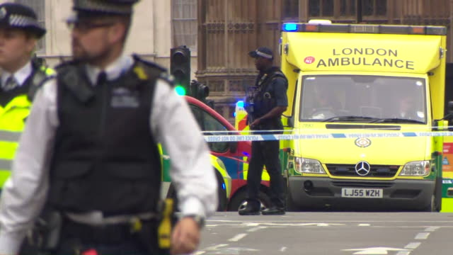 armed police and emergency vehicles outside the houses of parliament after a car crashed into security barriers during a suspected terror attack - シティ・オブ・ウェストミンスター点の映像素材/bロール