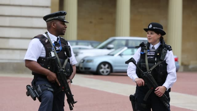 armed police officers guarding a gateway at buckingham palace, london, uk. - protection stock videos & royalty-free footage