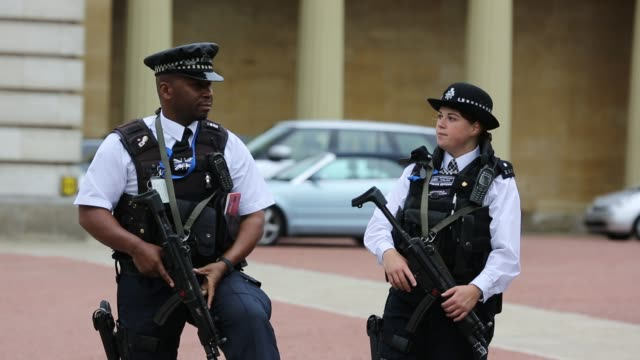 Armed police officers guarding a gateway at Buckingham Palace, London, UK.