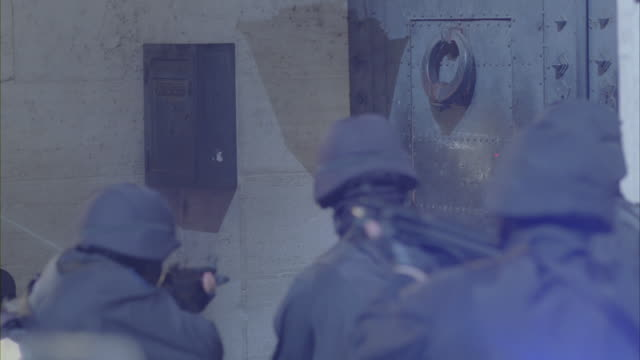 Armed police officers opening the door of a building.