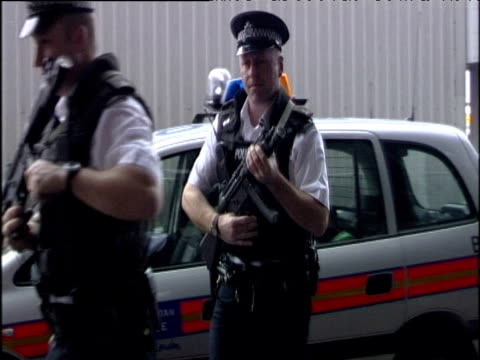stockvideo's en b-roll-footage met armed police officers wearing body armour walk into heathrow airport toting heckler and koch 9 mm sub machine guns london - number 9