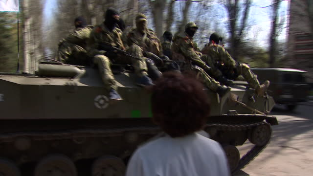 Armed proRussian separatists riding on military tank and walking through town of Sloviansk Ukraine