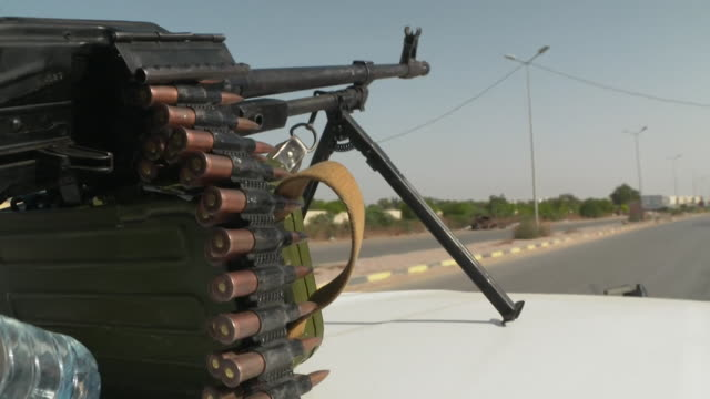 pov of armed rebel forces vehicle with close up of guns and bullets moving through streets of tripoli libya - ammunition stock videos & royalty-free footage