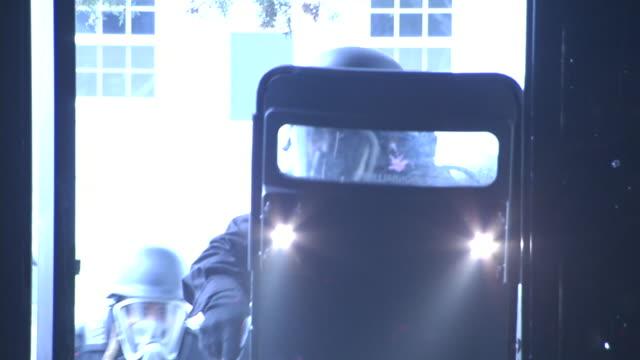 armed riot police enter a dark building. - 盾点の映像素材/bロール