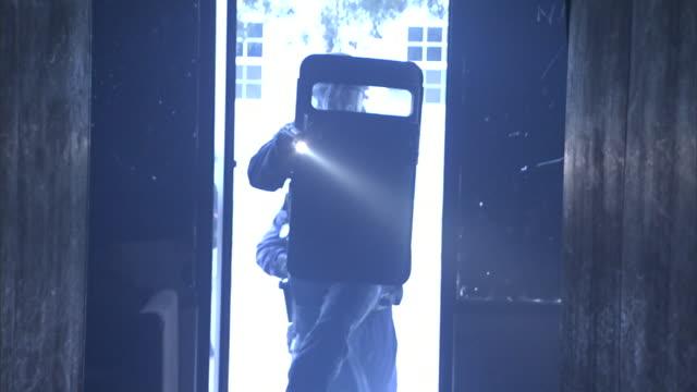 armed riot police use flashlights as they enter a dark building. - 盾点の映像素材/bロール