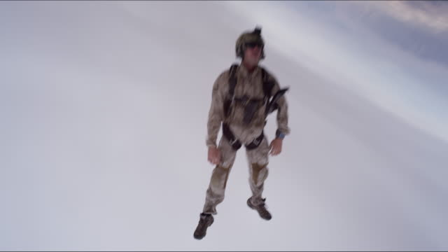 armed skydiver exits airplane over desert - free falling stock videos & royalty-free footage
