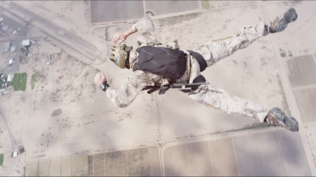 armed skydiver filmed from above - luftwaffe stock-videos und b-roll-filmmaterial