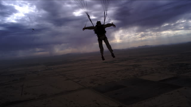 armed skydiver flies parachute over desert rain - 軍事点の映像素材/bロール