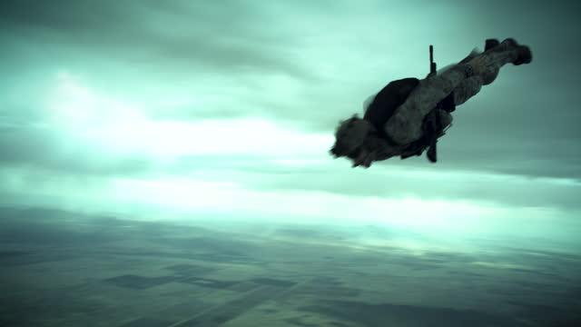 armed skydiver flies past camera - ominous stock videos & royalty-free footage