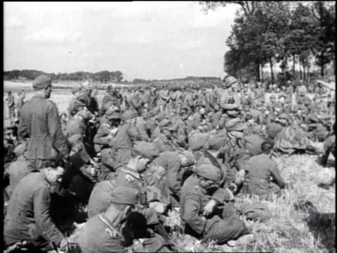 vidéos et rushes de armed soldier sitting on box guarding pows / large crowd of pows sitting on ground / pows sitting and waiting - world war 1