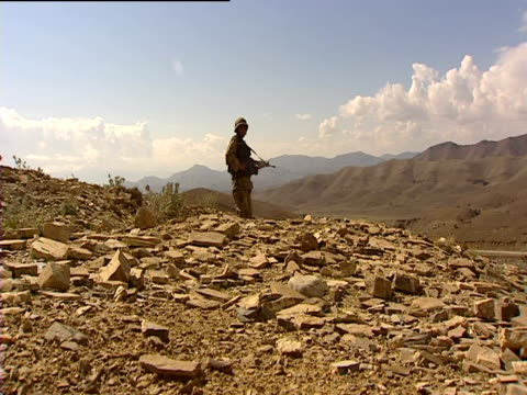 Armed soldier stands in the rocky mountains of North Waziristan