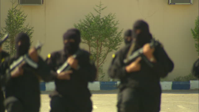 armed soldiers in black masks march on a military base in saudi arabia. - weaponry stock videos & royalty-free footage