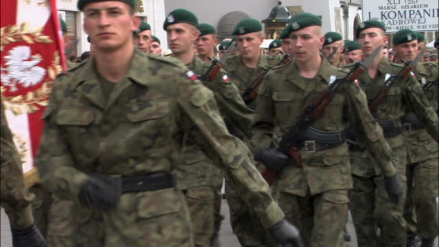 armed soldiers in camouflage gear marching with banner in military parade / krakow, poland - esercito video stock e b–roll