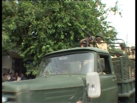 armed soldiers stand in a truck as it moves along a road - 武装犯点の映像素材/bロール