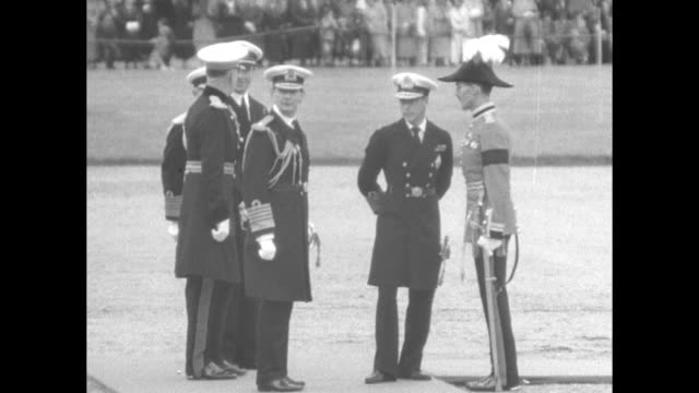 armed soldiers stand in formation / edward viii stands nearby / troop marches / king watches from sideline / soldiers stand in formation, lift hats... - エドワード8世点の映像素材/bロール