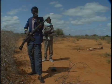 Armed Somali men walk through streets of Mogadishu and in countryside