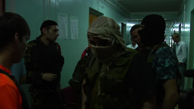 armed ukrainian separatists walk through hallway in polling station in donetsk region - 迷彩柄点の映像素材/bロール