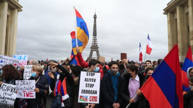 """armenian and french flags wave as a protester holds a sign that reads """"stop aliyev, stop erdogan"""" the eiffel tower in the background during a... - osteuropäische kultur stock-videos und b-roll-filmmaterial"""