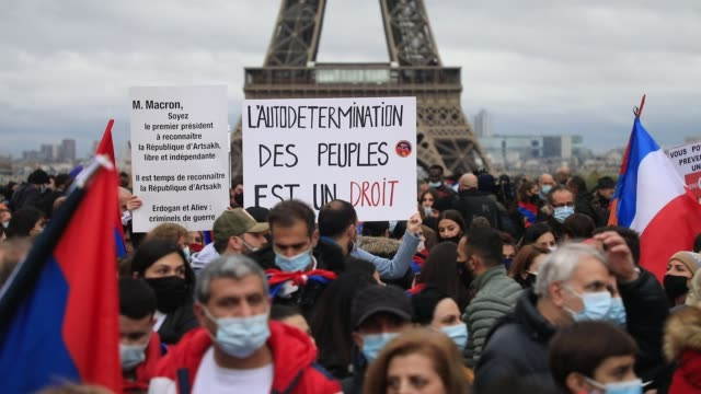 """armenian and french flags wave as a protester holds a sign that reads """"the self-determination of peoples is a right"""" , the eiffel tower in the... - osteuropäische kultur stock-videos und b-roll-filmmaterial"""