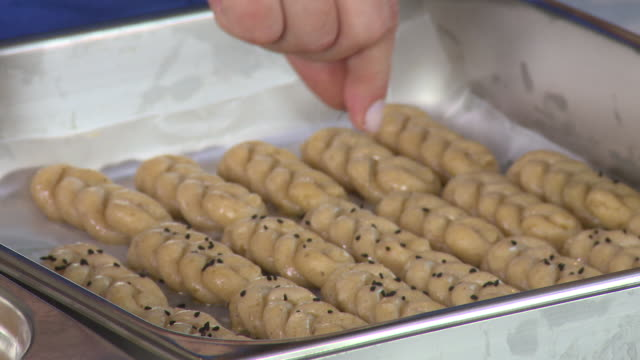 armenian cookies. hand-held view of a woman's hands sprinkling cumin seeds on a tray of braided zadigi kahke, armenian easter cookies. - moulding a shape stock videos & royalty-free footage