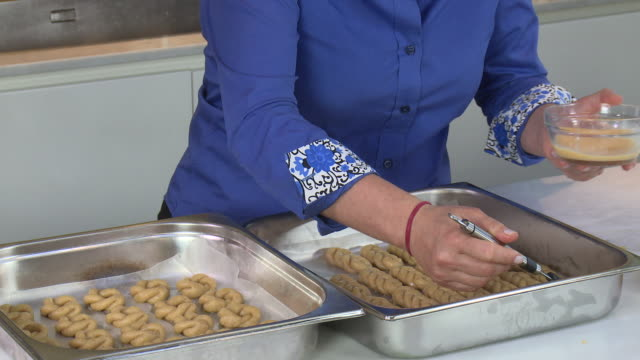 armenian cookies. view of a woman's hands brushing egg wash on a tray of zadigi kahke, armenian easter cookies. - moulding a shape stock videos & royalty-free footage