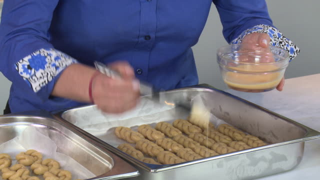 armenian cookies. view of a woman's hands brushing egg wash on a tray of braided zadigi kahke, armenian easter cookies. - moulding a shape stock videos & royalty-free footage