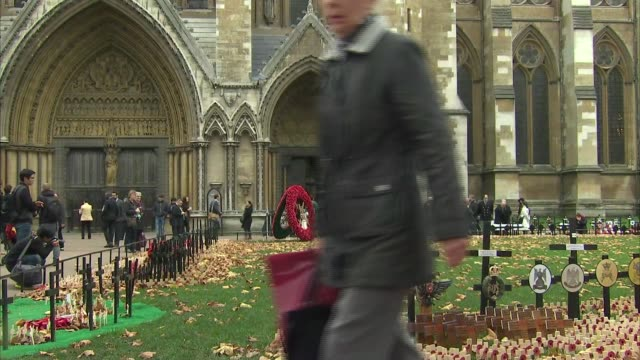 armistice day at westminster abbey; england: london: westminster abbey: ext close-up commemorative poppies / westminster abbey entrance / giant poppy... - armistice stock videos & royalty-free footage