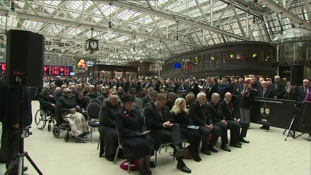 armistice day commemorations; scotland: glasgow central station: int crowd sitting in silence as last post played sot - armistice stock videos & royalty-free footage