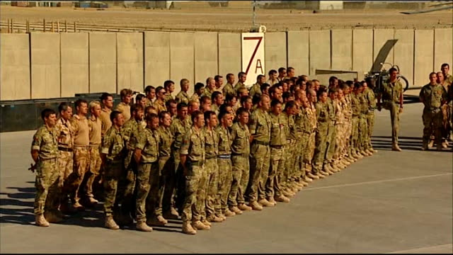armistice day marked at camp bastion helicopter flying in sky troops gathered in foreground / soldier laying wreath at cross / padre pays tribute to... - padre stock videos & royalty-free footage