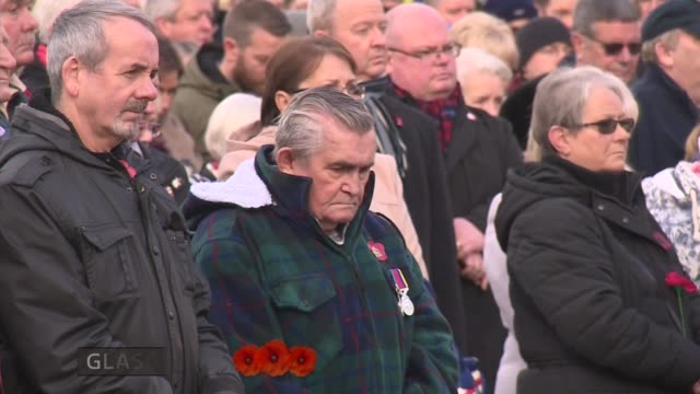 armistice day marked scotland glasgow ext members of public stand for minute's silence at armistice day ceremony - armistice stock videos & royalty-free footage