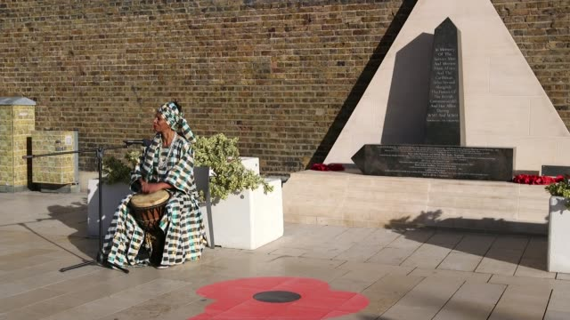 Tributes paid to AfricanCaribbean soldiers in Brixton ENGLAND London Brixton Windrush Square EXT Woman playing drums while singing SOT