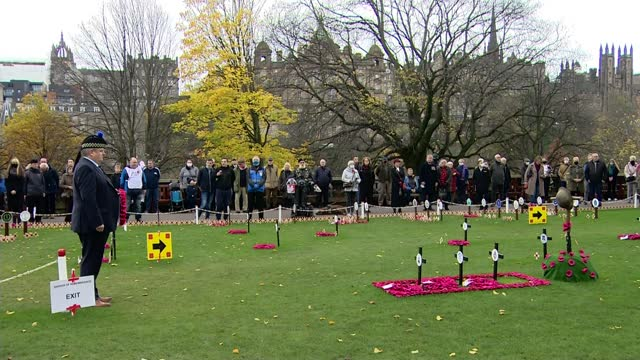 marks socially distanced armistice day amid covid-19 pandemic; scotland: edinburgh: ext gv people standing in silence during remembrance ceremony - armistice stock videos & royalty-free footage
