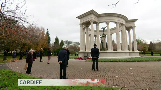 marks socially distanced armistice day amid covid-19 pandemic; wales: cardiff: ext gv people standing in silence during remembrance ceremony - armistice stock videos & royalty-free footage