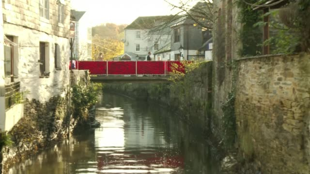 WWI Centenary marked at services at Cenotaph and across world ENGLAND Cornwall Truro EXT Bridge over River Allen covered in knitted poppies Close...