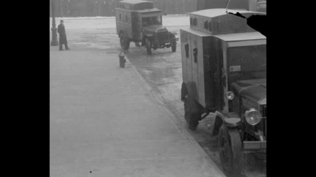 vs armored car leaves dock area driving on icy street the vehicles come to stop at curb armed guards leave truck and stand by as the heavy boxes are... - armored truck stock videos and b-roll footage