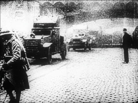 vídeos de stock, filmes e b-roll de b/w 1923 armored cars driving on city street / french occupation of germany's ruhr district - 1923