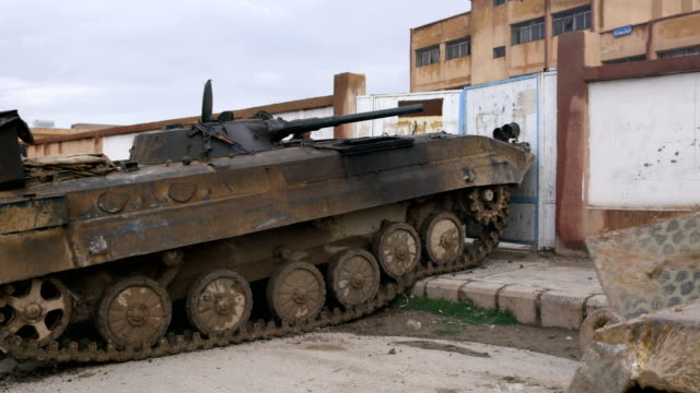 a ypg armored tank drives though the walls of a former isis military operations center during the battle to liberate the city of al shaddadeh in... - storage tank stock videos & royalty-free footage
