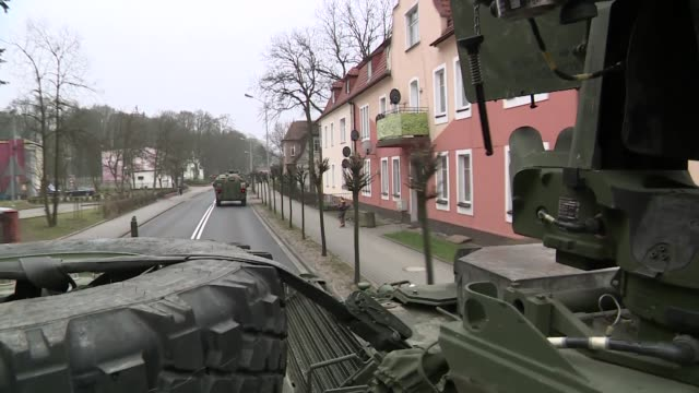 stockvideo's en b-roll-footage met armored transport convoy passing through a town - informatiebord