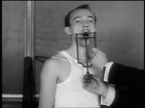 vídeos de stock, filmes e b-roll de b/w 1932 ms arms of man demonstrating jaw-breaking torture device on another man - tortura
