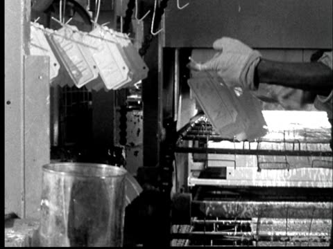 vidéos et rushes de 1956 ms arms of man taking hanging license plates and placing them on conveyor to be painted/ lansing, kansas  - 1956