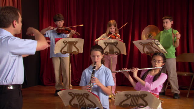 arms of music teacher conducting children during band practice / teacher stepping into frame / signaling children to finish piece / everyone bowing / los angeles, california - probe stock-videos und b-roll-filmmaterial